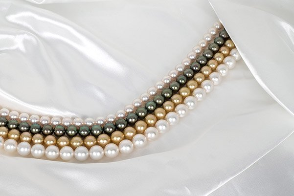 White and Gold south sea pearl necklaces next to Japanese Akoya and black Tahitian strands